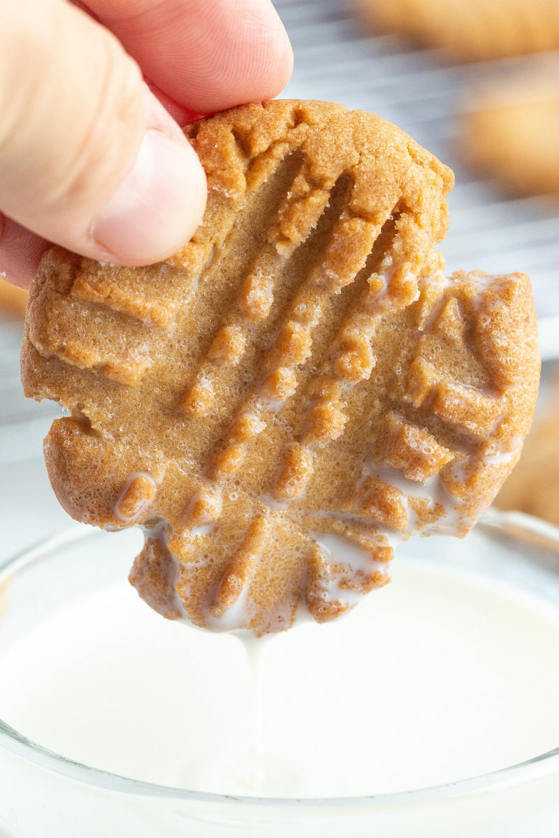 peanut butter cookie dipped in glass of milk