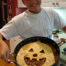 recipeboy holding jack o lantern sloppy joe pie in a skillet