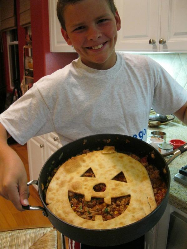 recipeboy holding skillet of jack o lantern sloppy joe pie