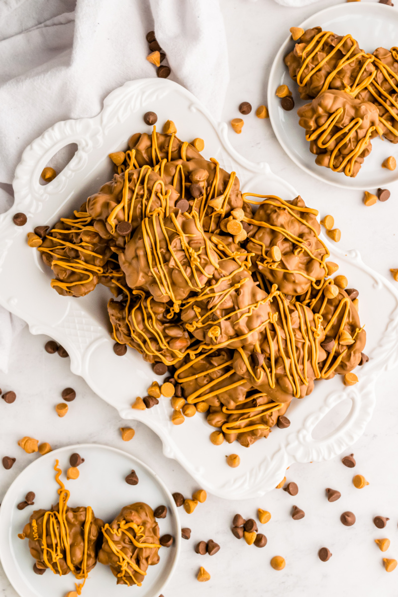 chocolate butterscotch peanut clusters stacked on white plate
