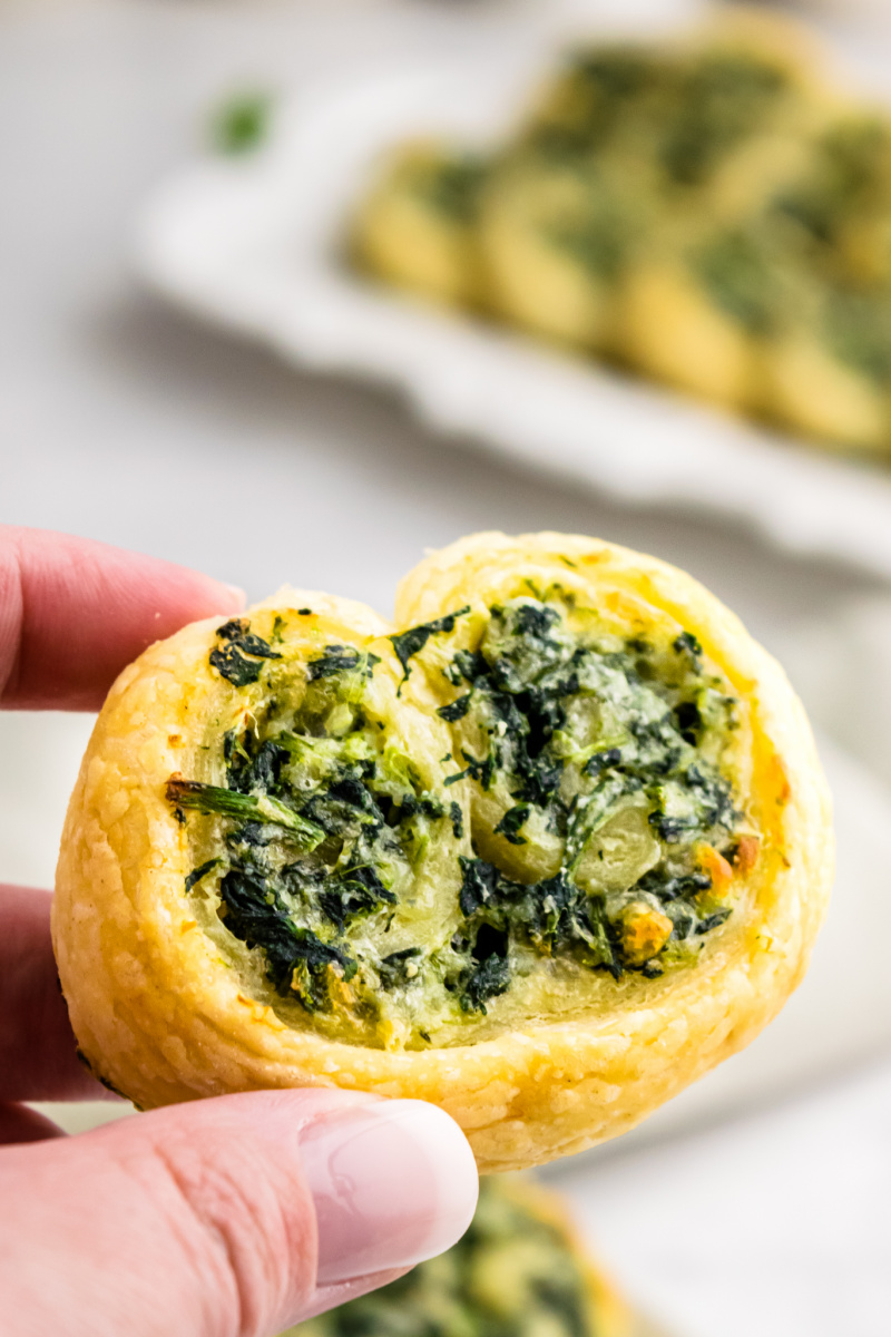 fingers holding one spinach palmier appetizer
