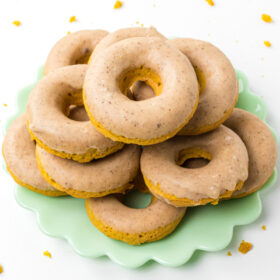 baked pumpkin donuts stacked on a green platter