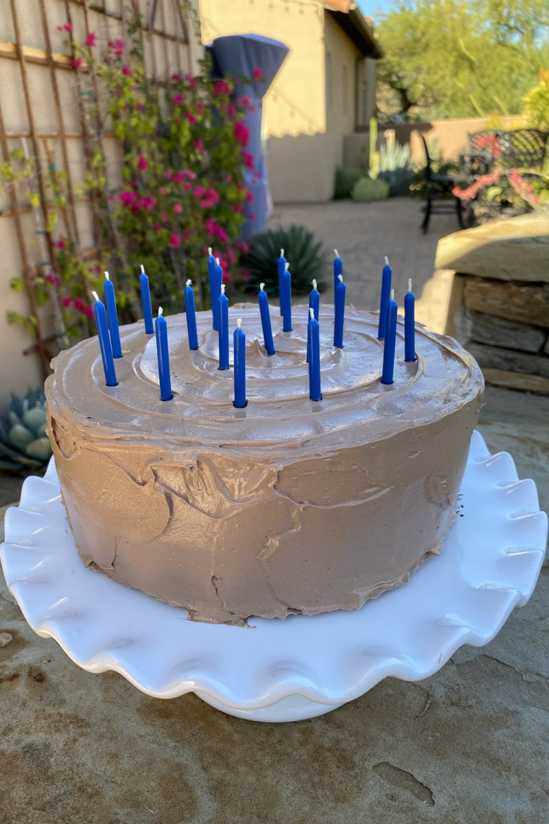 chocolate birthday cake with candles on a white cake platter