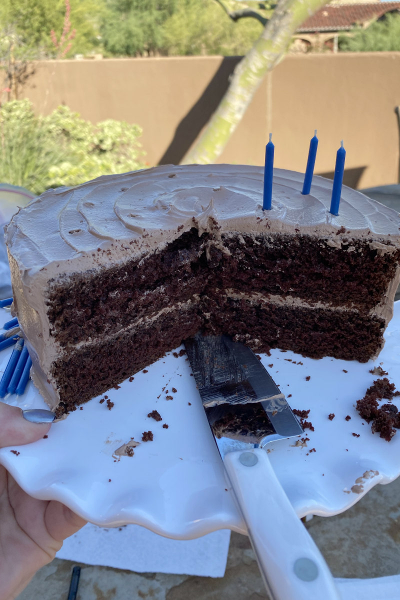 Chocolate Cake on a white platter sliced open to see the inside. Sharp knife sitting on the cake plate. Candles on top. Backyard scene.