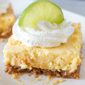 key lime bar on a white plate garnished with whipped cream and a lime wedge
