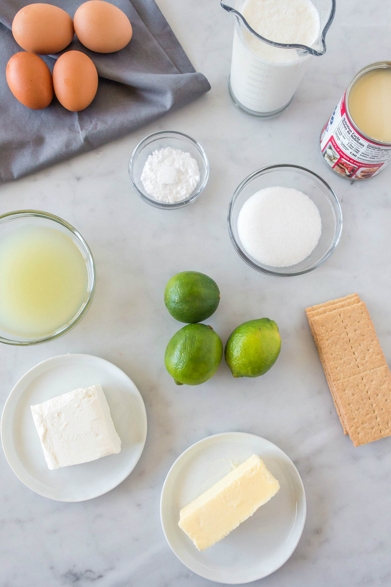 overhead shot of ingredients needed for key lime bars on a white background and displayed in glass bowls