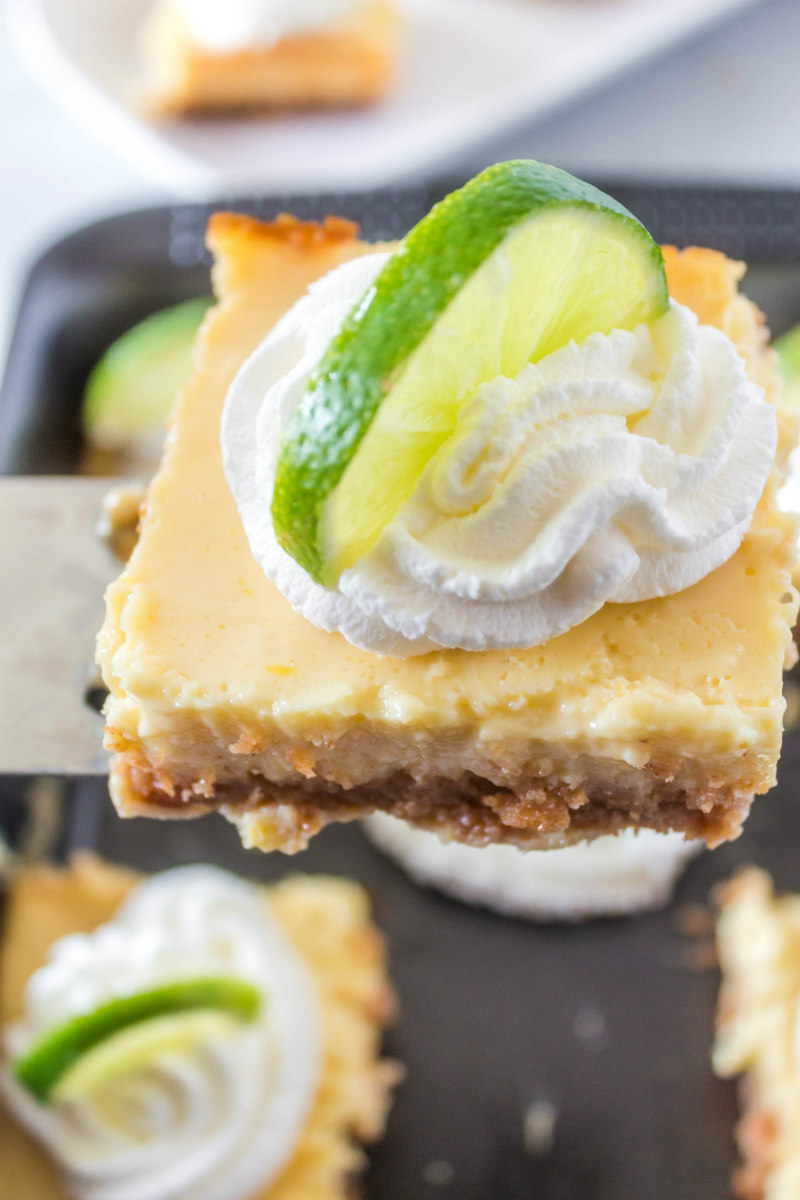 serving of key lime bars garnished with whipped cream and lime wedge