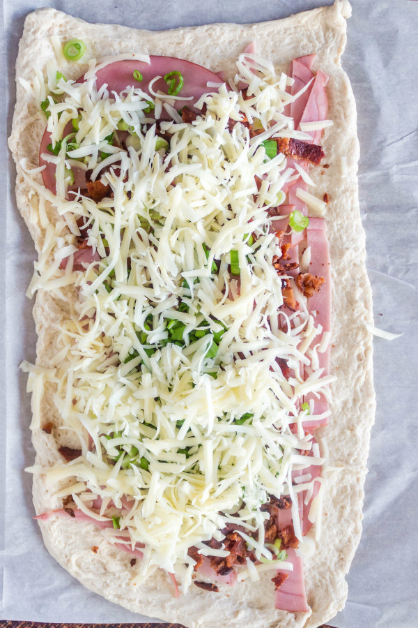 rolled out dough with ham and swiss cheese and other stromboli ingredients spread on top