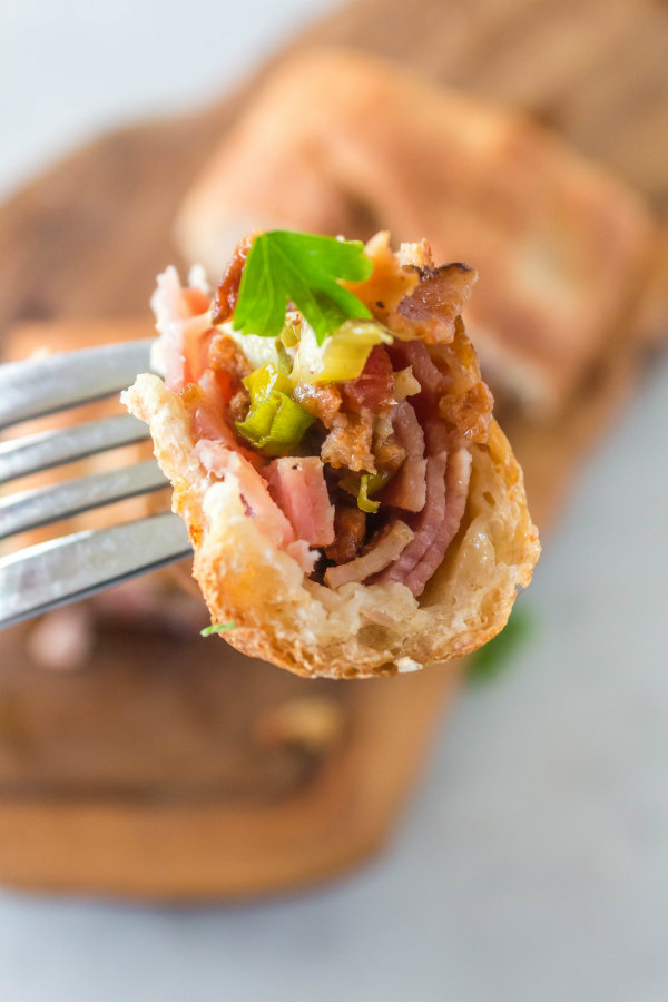 A bite with a fork of Ham and Swiss Stromboli