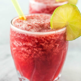 three cherry lime slushies garnished with lime and with a straw