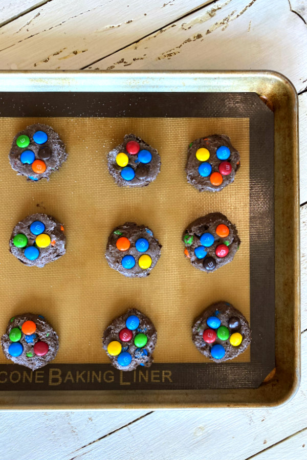 chocolate cake mix m&M cookies on a silpat lined baking sheet ready for the oven