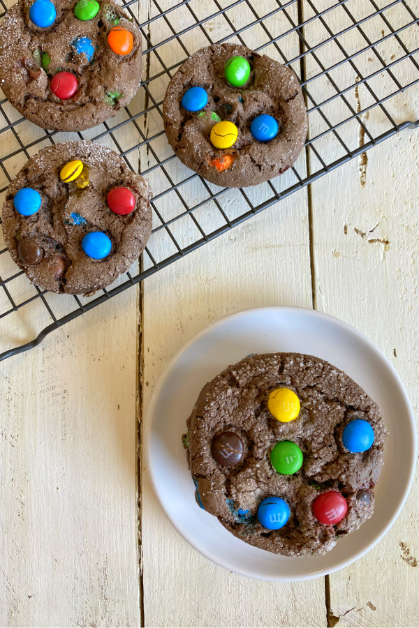 Chocolate cake mix M&M cookies on a cooling rack with a small white plate with a cookie on it alongside
