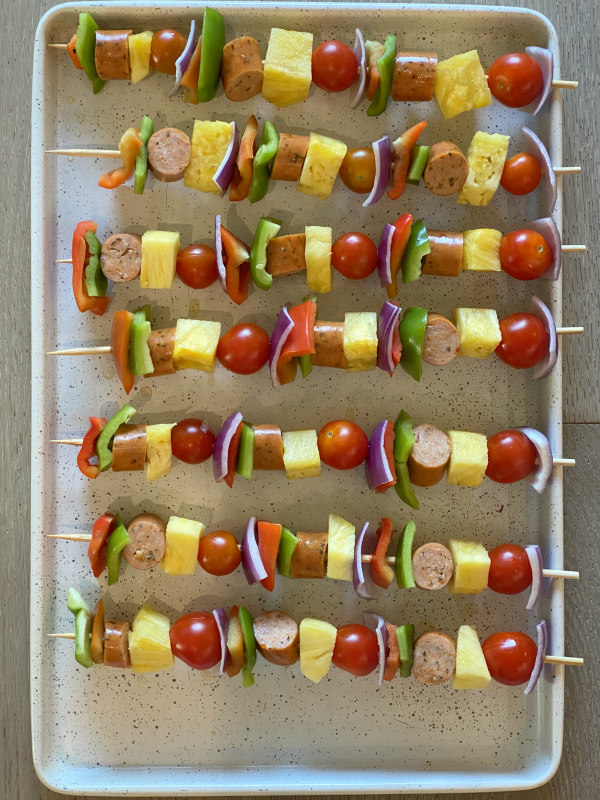 hawaiian chicken sausage kabobs on a sheet pan ready for the grill