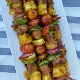 hawaiian chicken sausage kabobs stacked on a white platter set on a white/blue striped napkin