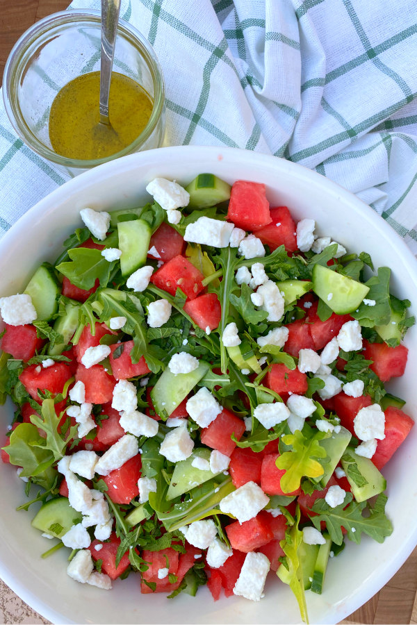 white bowl of watermelon cucumber and feta arugula salad displayed on a white and green plaid napkin