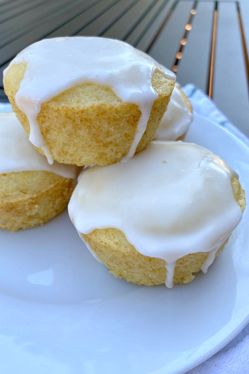 pile of three glazed lemon muffins displayed on a white plate