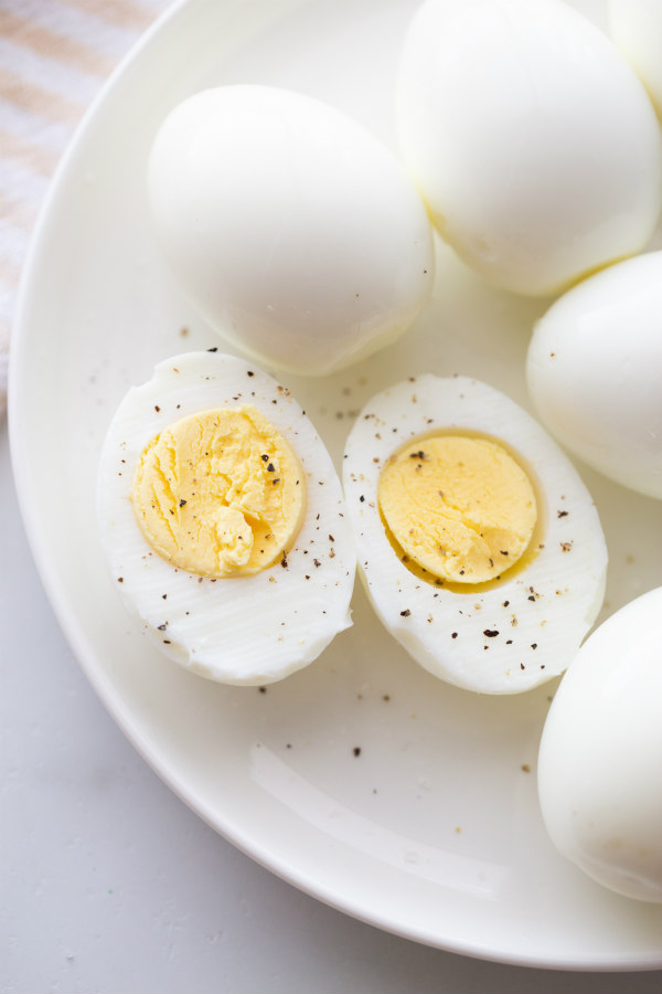 hard boiled eggs cut in half and displayed on a white plate with other whole hard boiled eggs. sprinkled with salt and pepper.