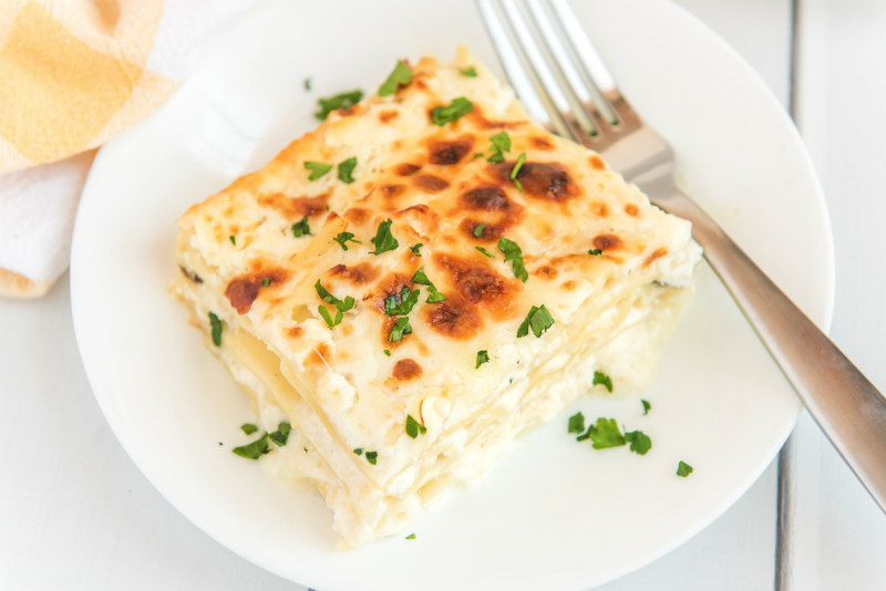slice of white chicken lasagna on a white plate