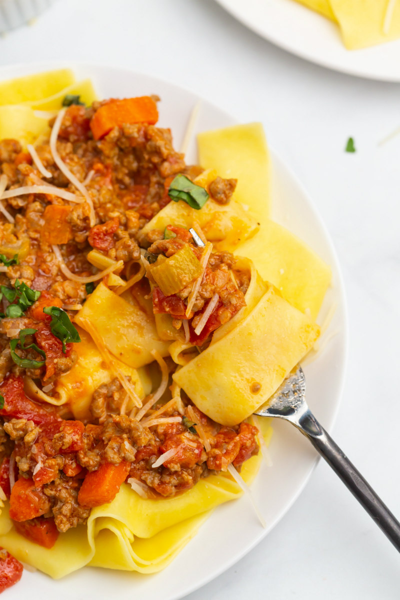 forkful of pappardelle bolognese on a plate