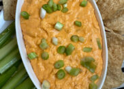 buffalo chicken dip in white bowl surrounded by celery and chips