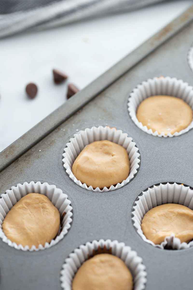 showing process of making peanut butter cups in muffin tin- adding peanut butter