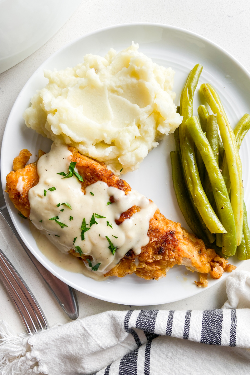 chicken fried chicken plated with potatoes and green beans