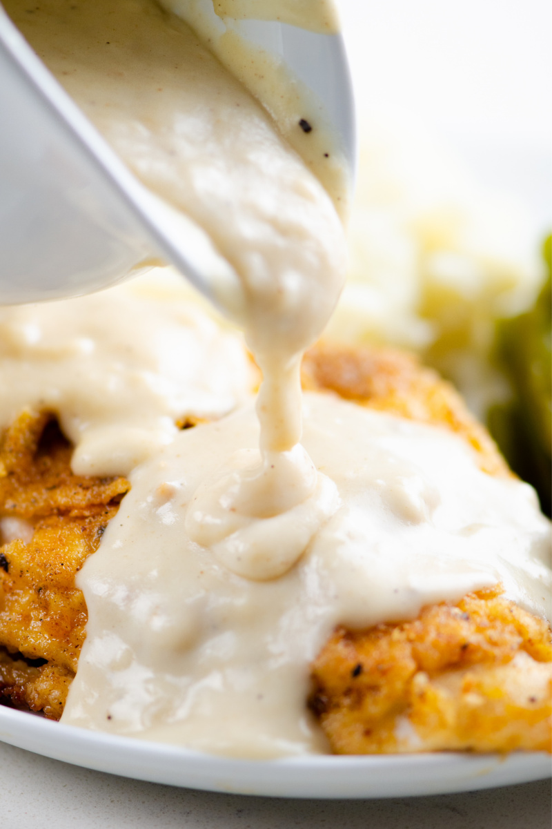 pouring country gravy over fried chicken