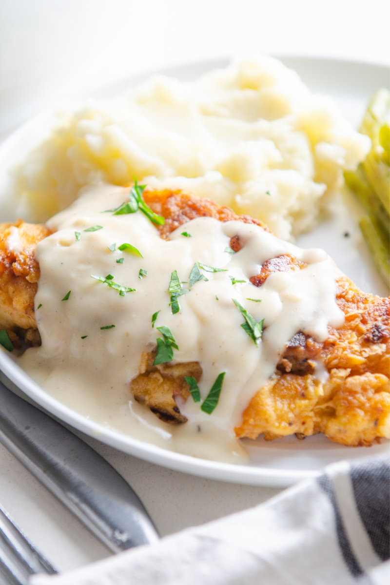 fried chicken covered with white gravy
