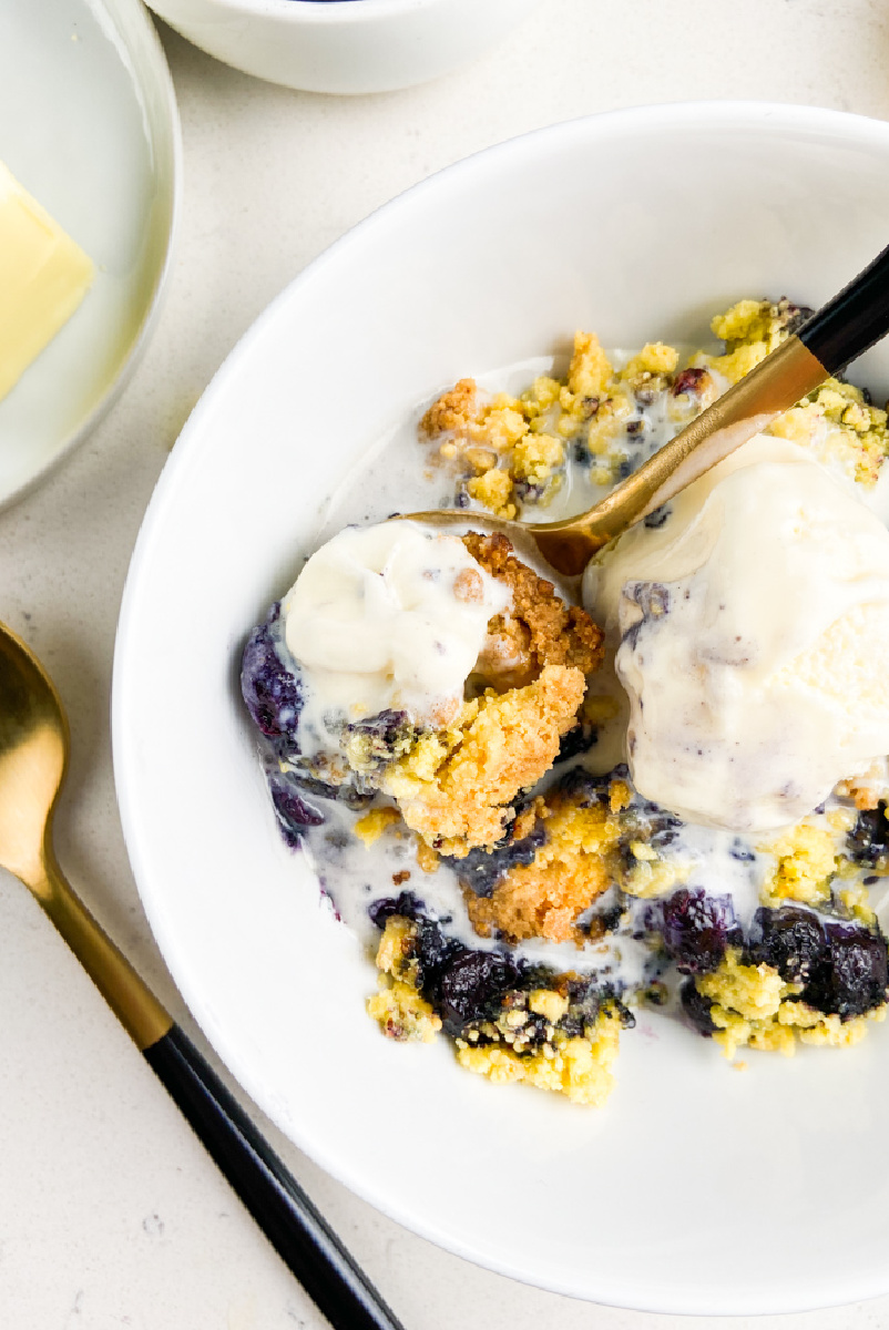 blueberry cobbler in white bowl with ice cream