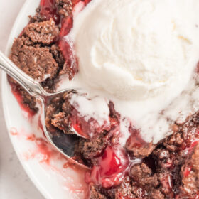 chocolate cherry dump cake with ice cream and spoon on white plate
