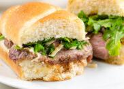 french onion steak sandwiches on white plate