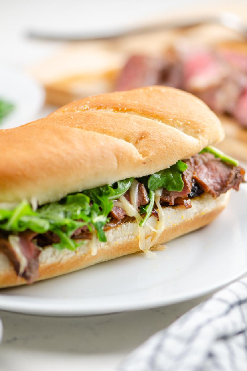 steak sandwich on long roll on white plate