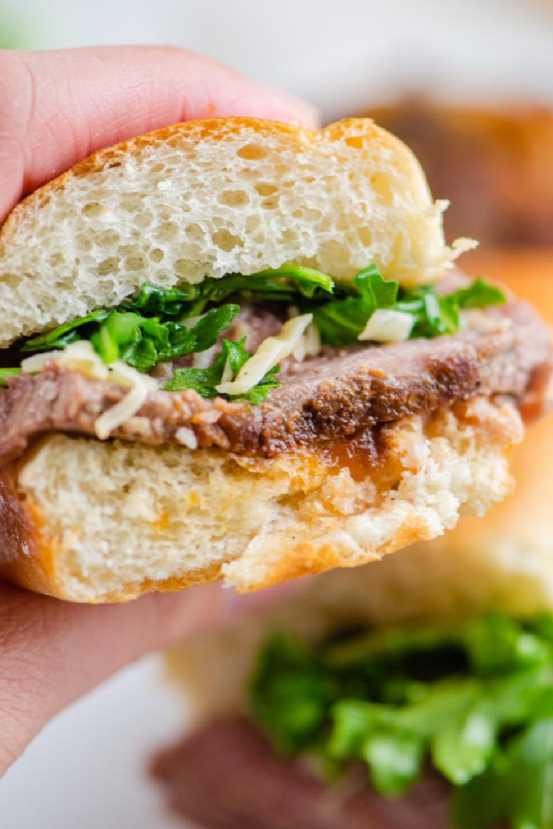 hand holding steak sandwich