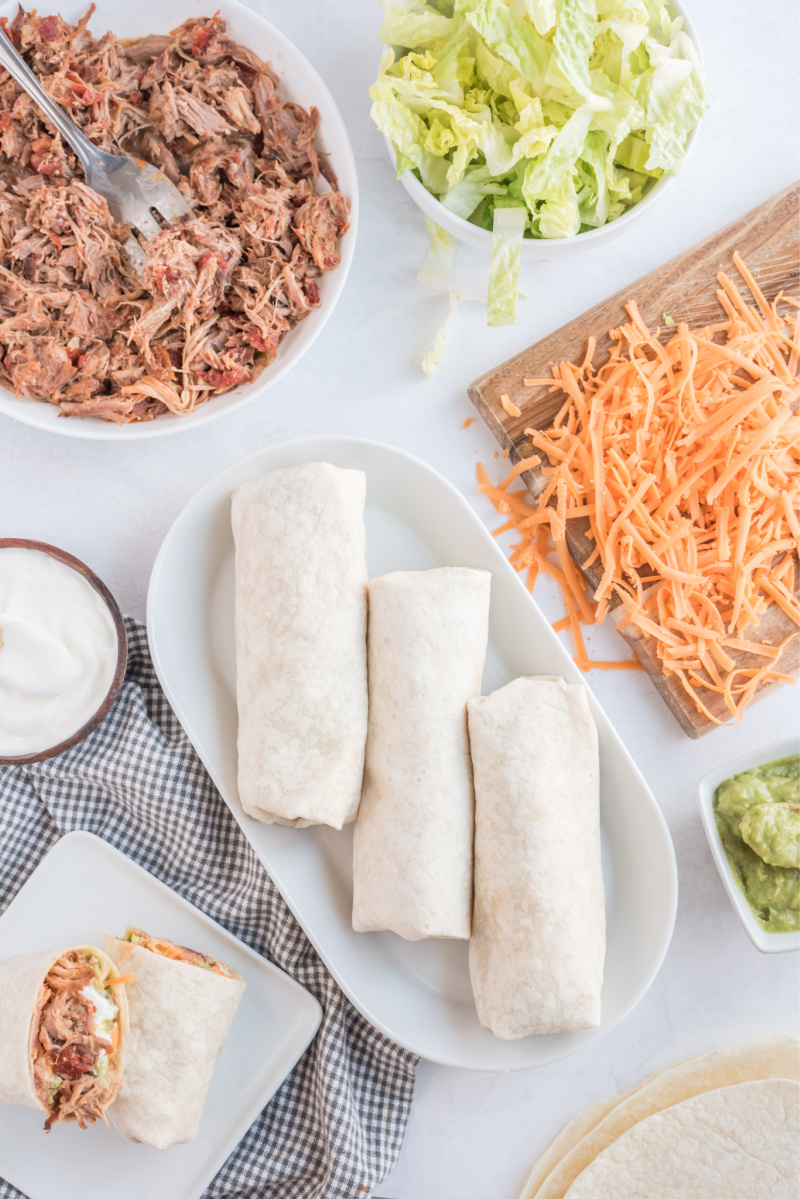 burritos wrapped up and surrounded by fixings