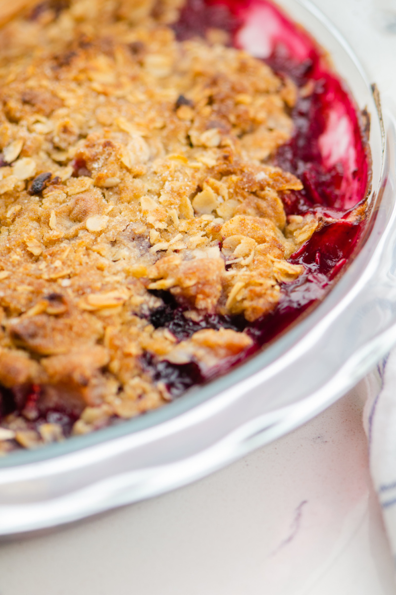 pear and berry crisp in a white casserole dish