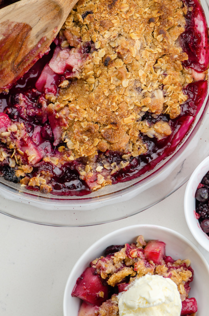 pear and berry crisp and one serving with ice cream beside it