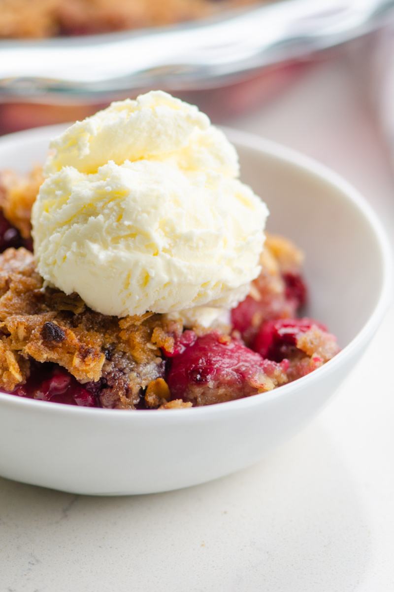 pear and berry crisp in a white bowl with ice cream