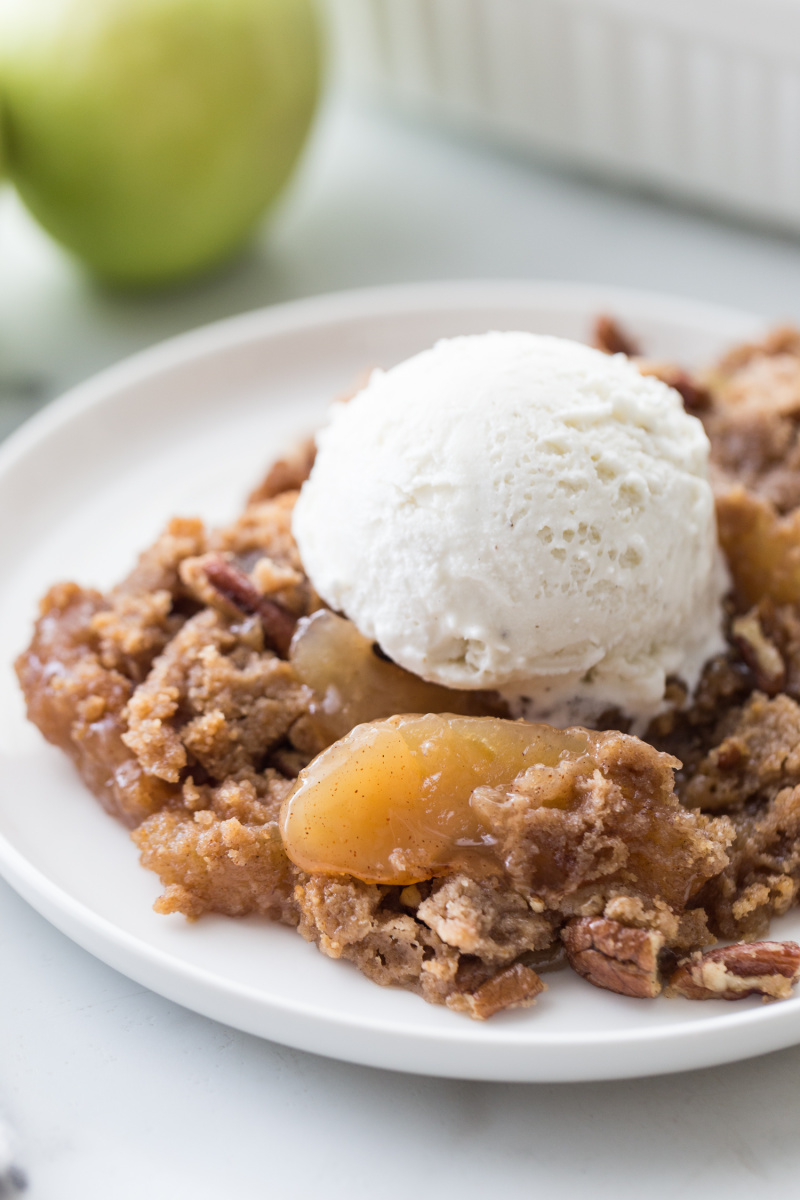serving of caramel apple dump cake on plate with ice cream